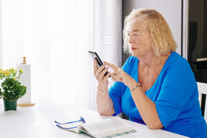 elderly-woman-checking-text-messages-DFU3P92